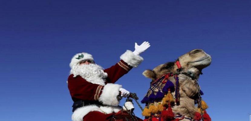 بابا نويل يمتطي جملا ويوزع أشجار عيد الميلاد في القدس